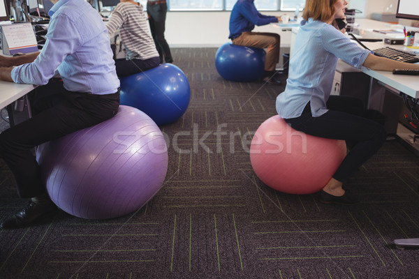 Low section of business people sitting on exercise balls while working at office Stock photo © wavebreak_media