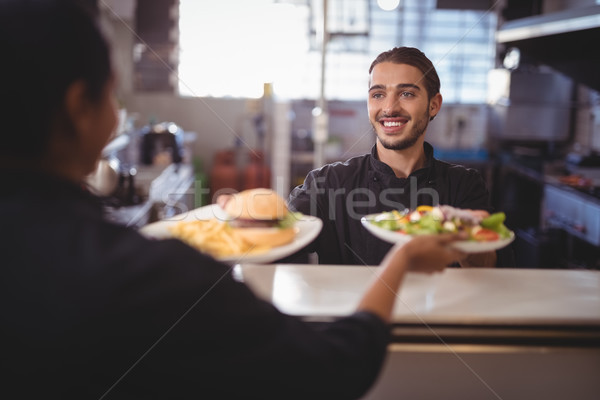 Smiling young waiter giving food to waitress at counter Stock photo © wavebreak_media