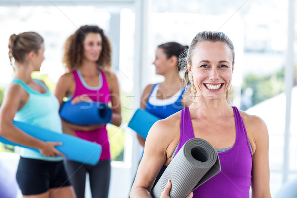 Portrait of cheerful woman holding exercise mat and smiling Stock photo © wavebreak_media