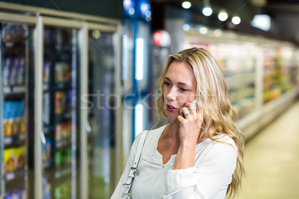 Szőke nő telefonbeszélgetés áruház üzlet nő boldog Stock fotó © wavebreak_media