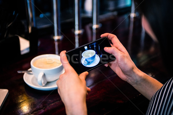Woman taking a picture of coffee with smartphone Stock photo © wavebreak_media