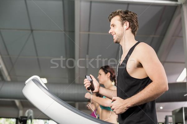 笑みを浮かべて 筋肉の 男 トレッドミル 音楽を聴く ジム ストックフォト © wavebreak_media