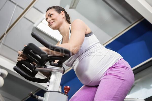 Pregnant woman using exercise bike Stock photo © wavebreak_media