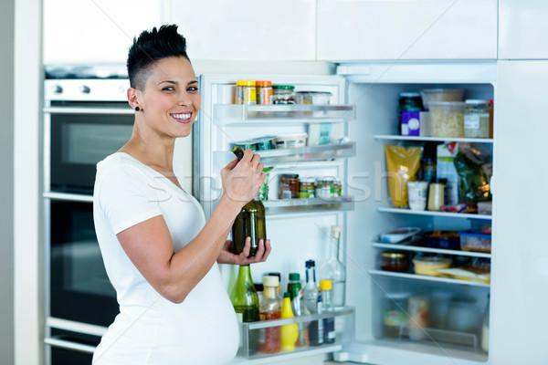 Mulher grávida alimentação picles em pé abrir geladeira Foto stock © wavebreak_media