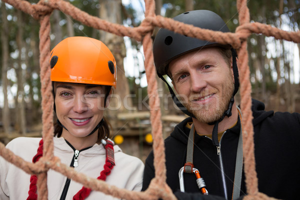 Portrait of smiling couple wearing safety helmet posing through a rope fence in the forest Stock photo © wavebreak_media