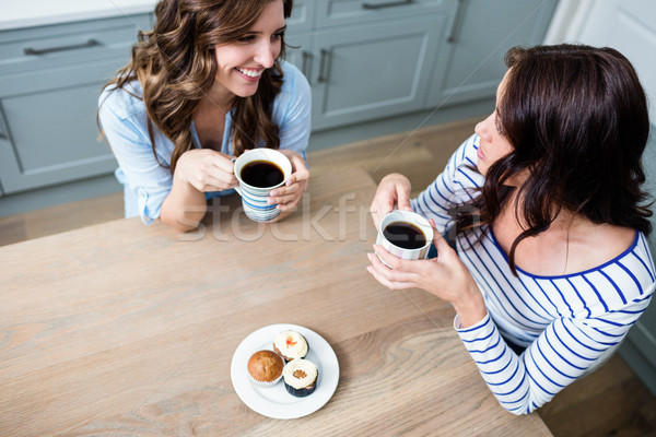 High angle view of female friends holding coffee mugs Stock photo © wavebreak_media