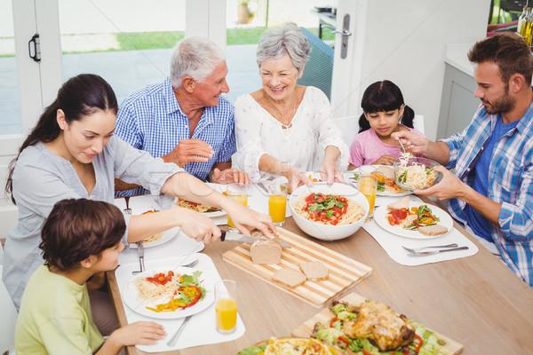 Mosolyog többgenerációs család étel étkezőasztal nő ház Stock fotó © wavebreak_media