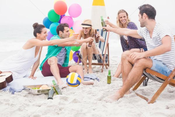 Csoport barátok pirít sör üvegek tengerpart Stock fotó © wavebreak_media