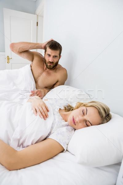 Aggressivo uomo guardando donna dormire letto Foto d'archivio © wavebreak_media