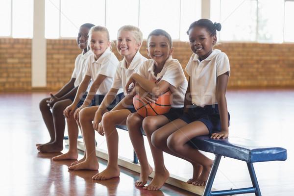 Sonriendo estudiantes sesión banco baloncesto escuela Foto stock © wavebreak_media