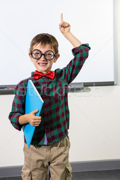 Portrait of cute boy with notebook raising hand in classroom Stock photo © wavebreak_media