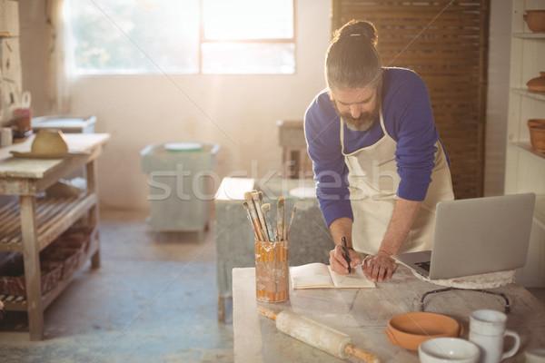 Potter writing on a book Stock photo © wavebreak_media