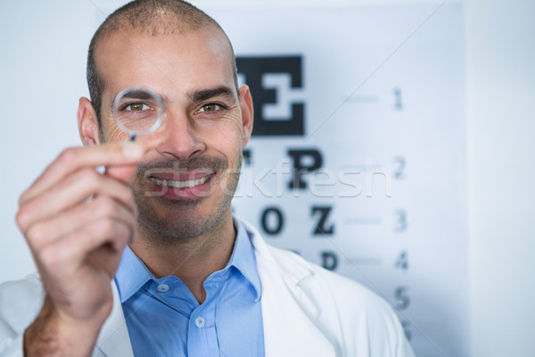 Male optometrist looking through magnifying glass Stock photo © wavebreak_media
