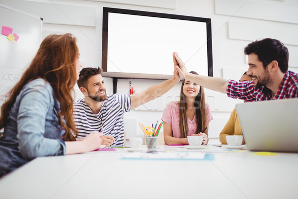 Male colleagues giving high-five in meeting at creative office Stock photo © wavebreak_media
