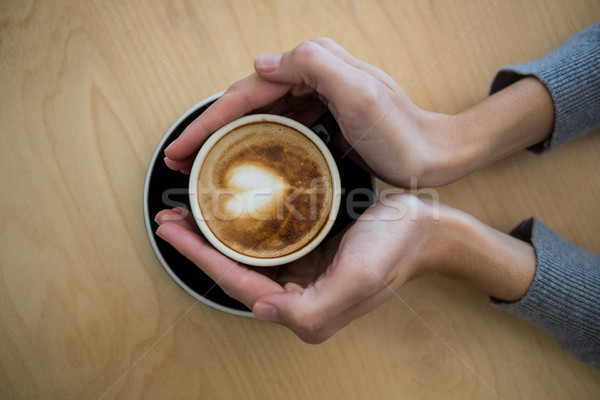 Woman holding cup of coffee on table Stock photo © wavebreak_media