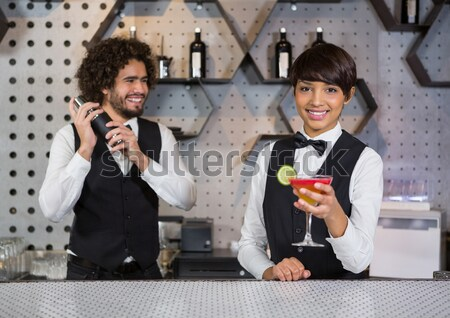 Waitress and waiter standing in bar counter with glass of cocktail Stock photo © wavebreak_media