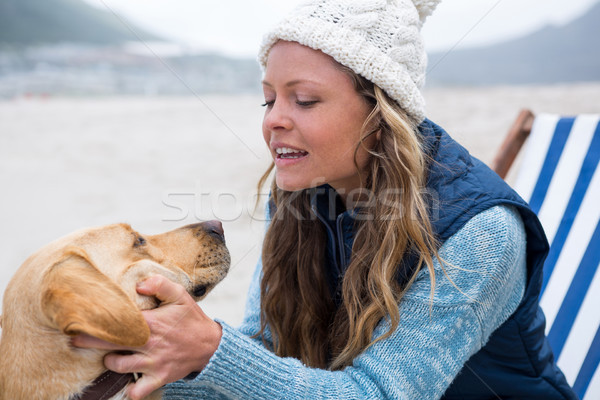 Woman pampering dog while sitting on chair Stock photo © wavebreak_media