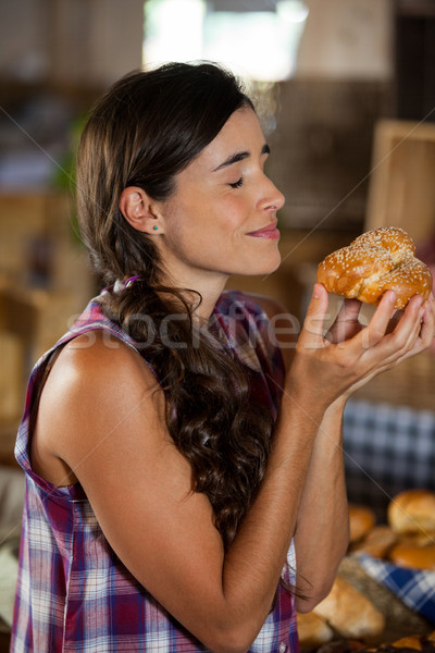 Smiling woman smelling a bread at counter Stock photo © wavebreak_media