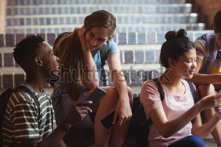 Portrait of smiling high school kids sitting on bench in basketball court Stock photo © wavebreak_media