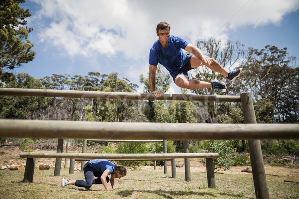 Man and woman jumping over the hurdles during obstacle course Stock photo © wavebreak_media