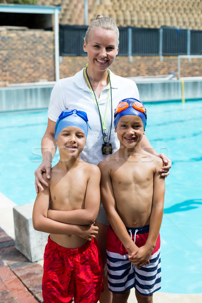 Swimming instructor with boys at poolside Stock photo © wavebreak_media