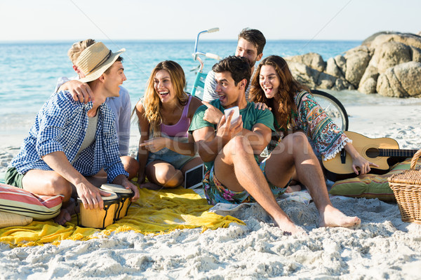 Friends laughing while sitting on shore Stock photo © wavebreak_media