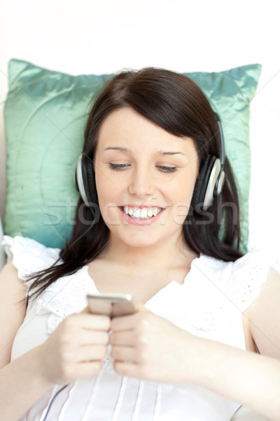 Wesoły młoda kobieta słuchania muzyki słuchawki telefon Zdjęcia stock © wavebreak_media