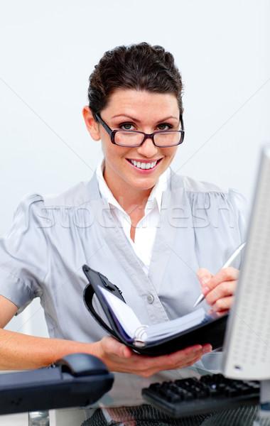 Positive business woman writting on her agenda Stock photo © wavebreak_media