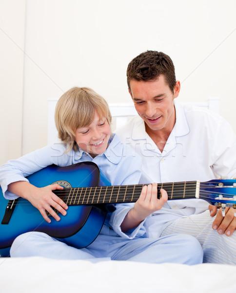 улыбаясь мало мальчика играет гитаре отец Сток-фото © wavebreak_media
