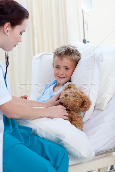 Female doctor listening to a child chest and a teddy bear Stock photo © wavebreak_media