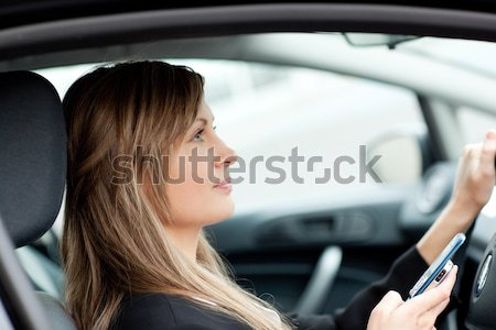 Beautiful businesswoman sending a text while driving  Stock photo © wavebreak_media