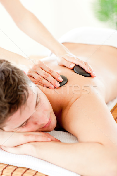 Stock photo: Resting man enjoying a massage with hot stone in a spa center