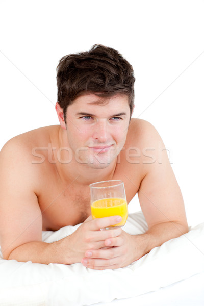 pretty man lying on his bed with a glass of orange juice at breakfast Stock photo © wavebreak_media