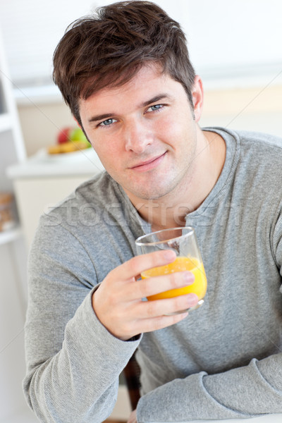 Atrakcyjny młody człowiek pitnej sok pomarańczowy kuchnia uśmiechnięty Zdjęcia stock © wavebreak_media