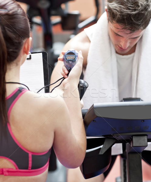 Close-up of a coach using a chronometer while man is doing physical exercises in a fitness centre Stock photo © wavebreak_media