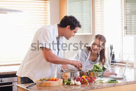 Attentive man giving a tomato to his girlfriend while having lunch in the kitchen  Stock photo © wavebreak_media