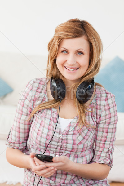 Happy blond-haired woman with headphones and mp3 player sitting in the living-room Stock photo © wavebreak_media