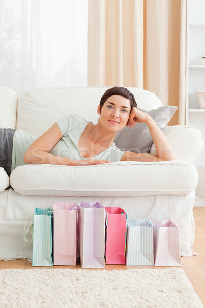 Stock photo: Portrait of a smiling woman with shopping bags in her living room