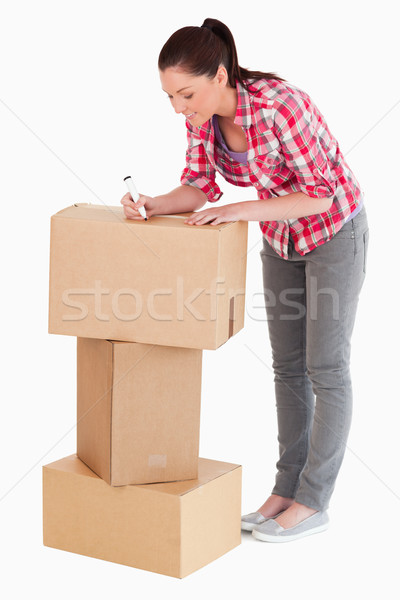 Gorgeous woman writing on cardboard boxes with a marker while standing against a white background Stock photo © wavebreak_media