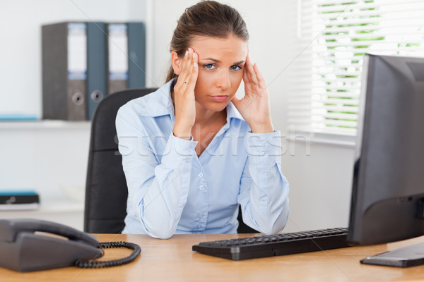 A stressed businesswoman is sitting at workplace in an office while looking into the camera Stock photo © wavebreak_media