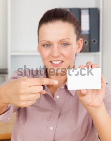 Blonde smiling businesswoman pointing at a card crouching behind her desk in her office Stock photo © wavebreak_media