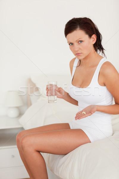 Sick woman showing pills in the bedroom Stock photo © wavebreak_media