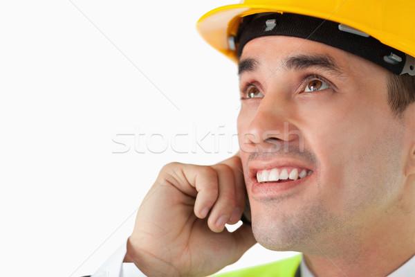 Close up of architect on the phone looking upwards against a white background Stock photo © wavebreak_media