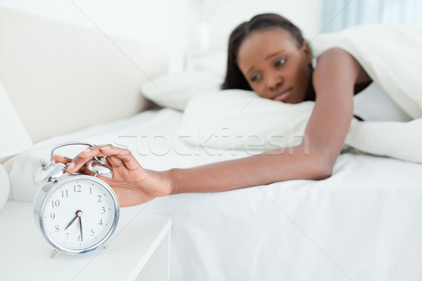 Woman switching off her alarm clock in her bedroom Stock photo © wavebreak_media