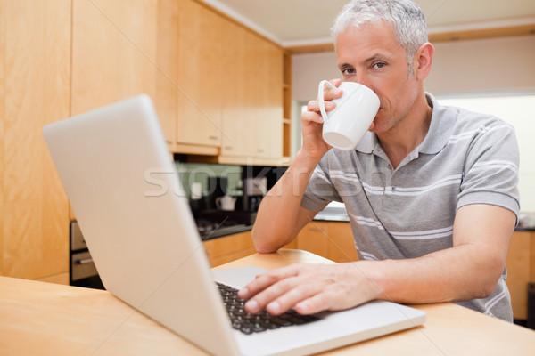Człowiek notebooka pitnej kawy kuchnia Internetu Zdjęcia stock © wavebreak_media