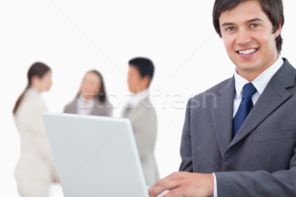 Smiling salesman with laptop and colleagues behind him against a white background Stock photo © wavebreak_media