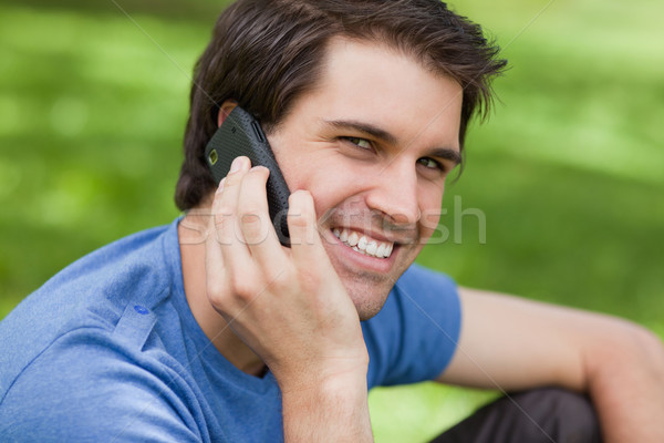 Smiling young man looking at the camera while using his mobile phone in a parkland Stock photo © wavebreak_media