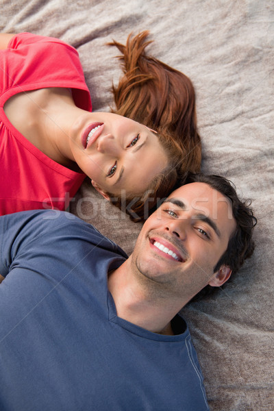 Close-up of two smiling friends lying next to each other as they look into the sky while on a grey q Stock photo © wavebreak_media