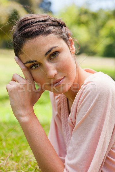 Woman with a serious expression tilting her head against her fingers as she lays on front in the gra Stock photo © wavebreak_media