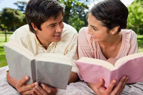 Man and a woman smiling at each other while reading books as they lie prone on a grey blanket in the Stock photo © wavebreak_media